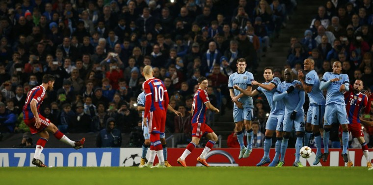 Bayern Munich's Xabi Alonso (L) scores a goal on free kick during their Champions League Group E soccer match against Manchester City in Manchester, November 25, 2014. (REUTERS/Darren Staples)