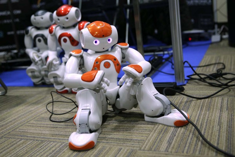 Humanoid robots sit on the floor during the International Conference on Humanoid Robots in Madrid November 19, 2014. (Andrea Comas/Reuters)
