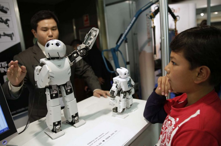 A boy looks at robots during the International Conference on Humanoid Robots in Madrid November 19, 2014. (Andrea Comas/Reuters)