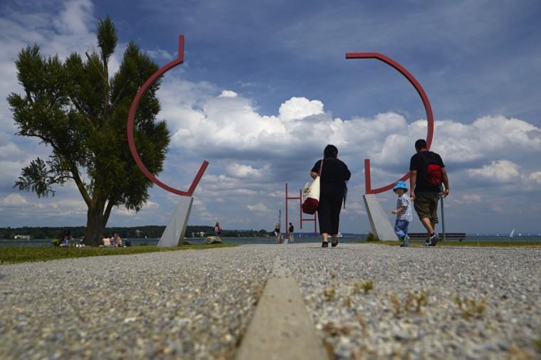 People walk past a sculpture by artist Johannes Doerflinger, through the border between Germany and Switzerland in Kreuzlingen near Konstanz May 14, 2014.