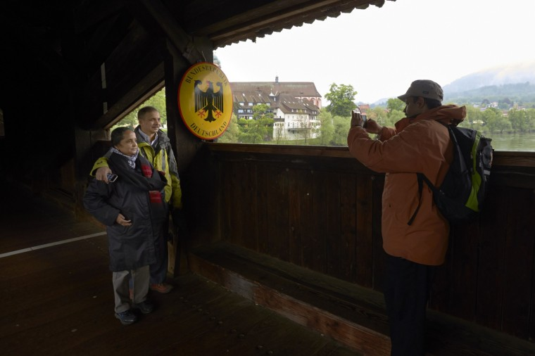 Tourists take a picture on a 400-year-old wooden bridge on the border between Switzerland (front) and Germany in Stein May 1, 2014.