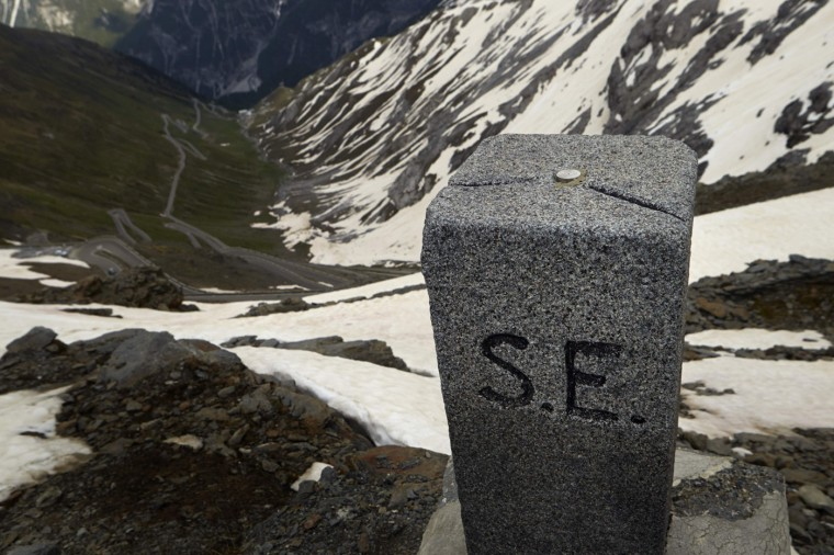 A marker stands at the Dreisprachenspitze (Three Languages Peak) in front of the road to the Stelvio Pass at the border between Italy (R) and Switzerland in Tschierv May 13, 2014.