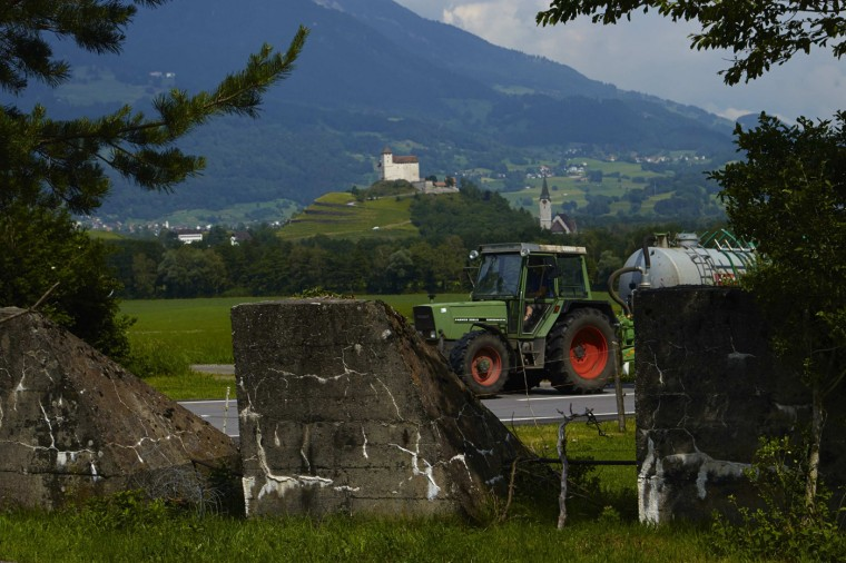 A tractor drives past WWII military defences, known as 'toblerone', at the border between Liechtenstein (behind) and Switzerland in Flaesch May 14, 2014.