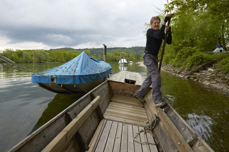 Peter Albrecht pushes his weidling boat on the Rhein river on the border between Switzerland (left bank) and Germany in the German enclave of Buesingen am Hochrhein near Schaffhausen May 2, 2014.