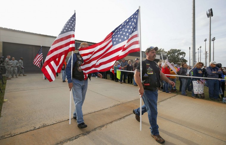 Members of the Patriot Guard Riders carry U.S. flags as an airplane bringing paratroopers with the 1st Brigade Combat Team, 82nd Airborne Division home from Afghanistan, arrives at Pope Army Airfield in Fort Bragg, North Carolina November 5, 2014. Approximately 300 troops arrived home after being deployed since February 2014, according to the military. (Chris Keane/Reuters)