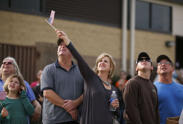 A woman waves a flag as she and others watch the airplane flying paratroopers with the 1st Brigade Combat Team, 82nd Airborne Division, as they return home from Afghanistan, at Pope Army Airfield in Fort Bragg, North Carolina November 5, 2014. Approximately 300 troops arrived home after being deployed since February 2014, according to the military. (Chris Keane/Reuters)
