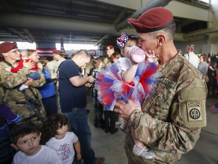 Sean Smith, a paratrooper with the 1st Brigade Combat Team, 82nd Airborne Division, kisses his daughter Olivia Rose Smith, 10 months, after returning home from Afghanistan at Pope Army Airfield in Fort Bragg, North Carolina November 5, 2014. Approximately 300 troops arrived home after being deployed since February 2014, according to the military. (Chris Keane/Reuters)