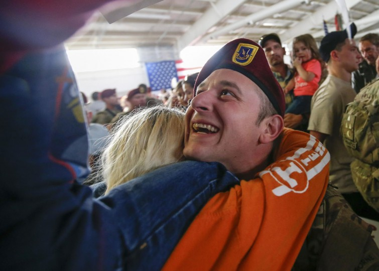 A paratrooper with the 1st Brigade Combat Team, 82nd Airborne Division, looks up at his son while sharing a hug with his wife after returning home from Afghanistan at Pope Army Airfield in Fort Bragg, North Carolina November 5, 2014. Approximately 300 troops arrived home after being deployed since February 2014, according to the military. (Chris Keane/Reuters)