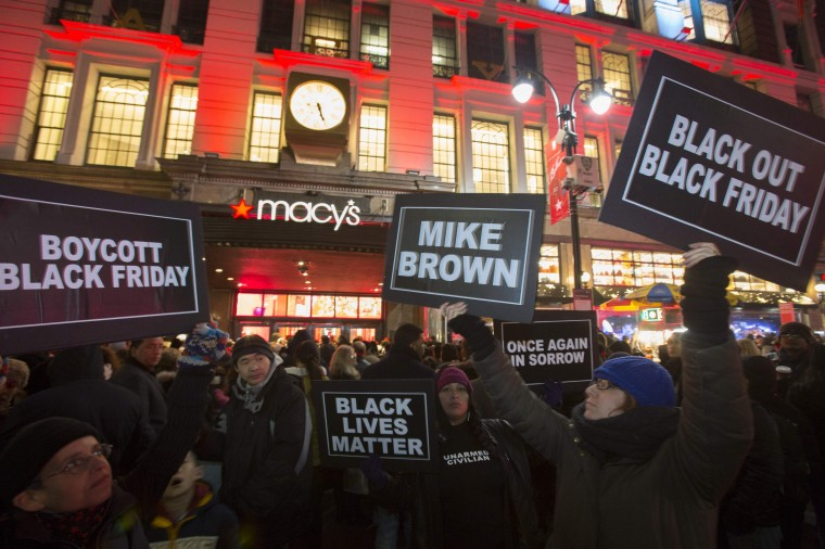 Protesters hold signs aloft outside Macy's before the kick off of Black Friday sales in New York November 27, 2014. Select stores opened Thursday to kick off the Black Friday sales, with the Friday after Thanksgiving typically being the busiest shopping day of the year in the U.S. The protesters were affiliated with the Ferguson movement and were protesting in response to a grand jury decision not to indict Police Officer Darren Wilson for the shooting death of Michael Brown. (Andrew Kelly/Reuters)