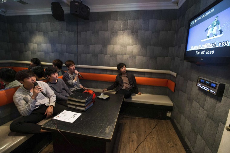 Sung Min See, 16, Jaewoong Lee, 17, Joon Kim, 16, and Jason Jung, 18, (L-R), who all emigrated from Seoul, South Korea, sing in a karaoke cafe in the Koreatown area of Los Angeles, California August 11, 2014.