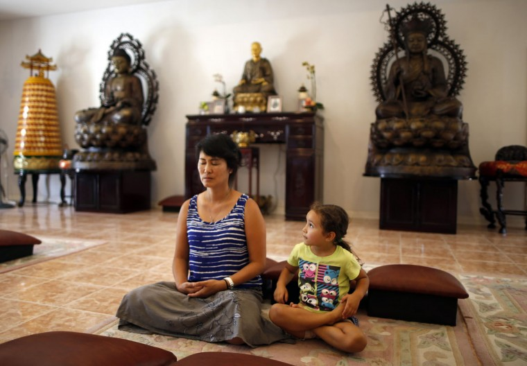 Sarah Kim (L), who emigrated from South Korea, meditates with Sabina Mayorga, 4, whose parents are from Mexico, at Lu Mountain Buddhist Temple in Rosemead, California August 15, 2014.