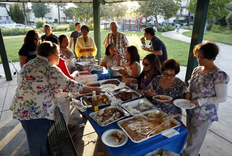 Retired professor Carlos Jainga, 71 (6th R) and his wife Estrella Jainga, 68, (L) attend a farewell party for their friend Dolores Saballo, 65, (R) who is returning to the Philippines, at a park in Torrance, California September 30, 2014.
