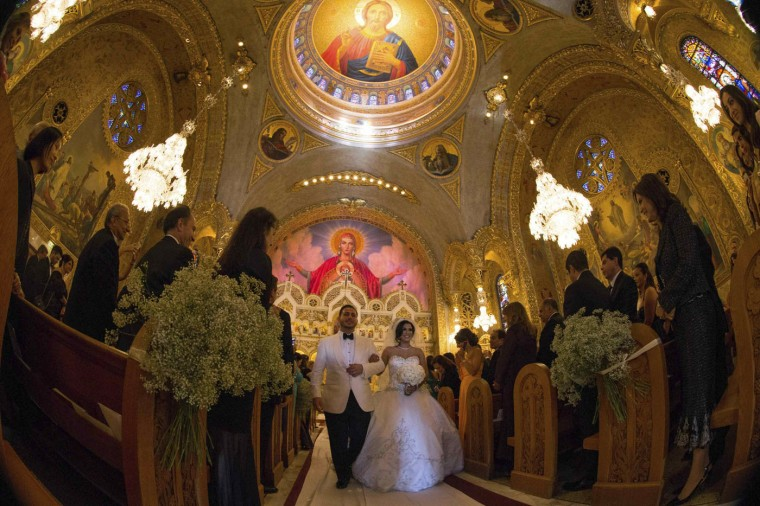 Megan Moshar (centre R), 26, who is of Persian, German and Filipino descent, walks down the aisle with her new husband George Safar, 27, whose parents are from Syria, at their wedding in Saint Sophia Greek Orthodox Cathedral in Los Angeles, California August 16, 2014.