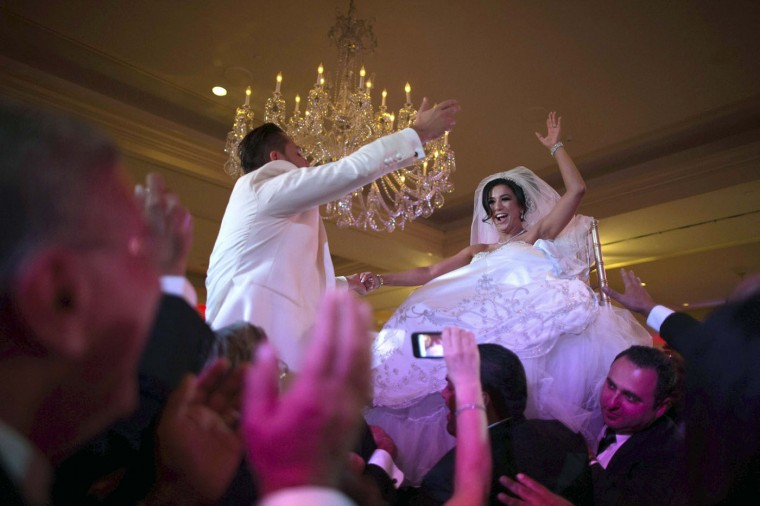 Megan Moshar (R), 26, who is of Persian, German and Filipino descent, dances with her husband George Safar, 27, whose parents are from Syria, as they are both lifted into the air during their wedding reception in Pasadena, California August 16, 2014.