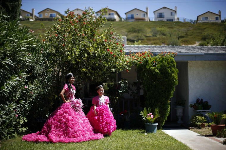 Mimi Pineda (L), 15, whose parents are from El Salvador, stands outside her aunt's house with Maybelin Ramirez, 6, before her quinceanera in Santa Clarita, California August 23, 2014. Quinceanera is a rite of passage celebrated on the fifteenth birthday of many female Latino teenager.