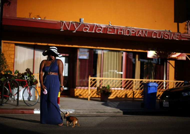 A woman poses for a friend's photo in the Little Ethiopia area of Los Angeles, California September 14, 2014.