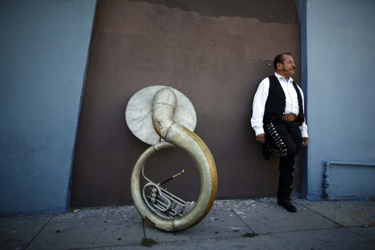 Mariachi musician Moises Rivera, 60, waits for a gig in the Boyle Heights area of Los Angeles, home to many Mexican and Central American migrants, in California August 9, 2014.