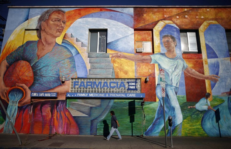 A man walks past a mural in the Echo Park area of Los Angeles, home to many Mexican and Central American migrants, in California August 5, 2014.