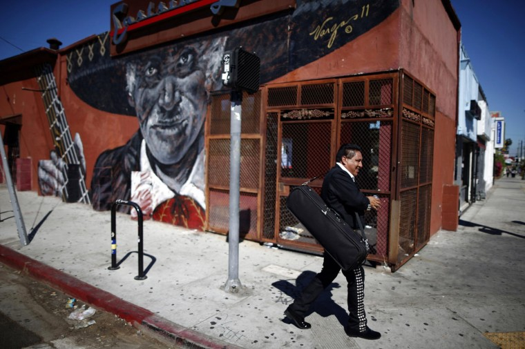 A mariachi musician walks past a mural in the Boyle Heights area of Los Angeles, home to many Mexican migrants, in California August 5, 2014.