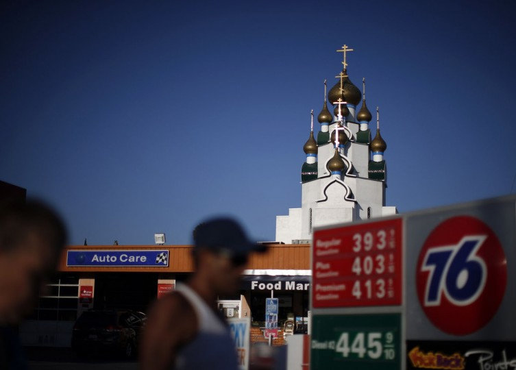 People walk past a gas station as a Russian Orthodox Church is seen in the distance in Hollywood, California August 11, 2014.