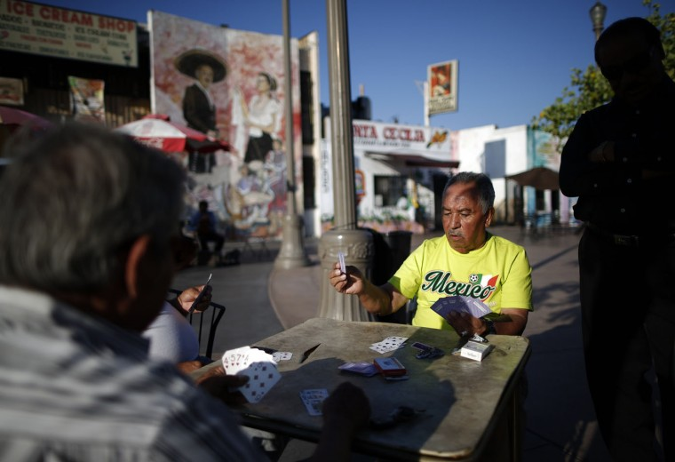 Men play cards in Mariachi Plaza in the Boyle Heights area of Los Angeles, home to many Mexican and Central American migrants, California August 9, 2014.