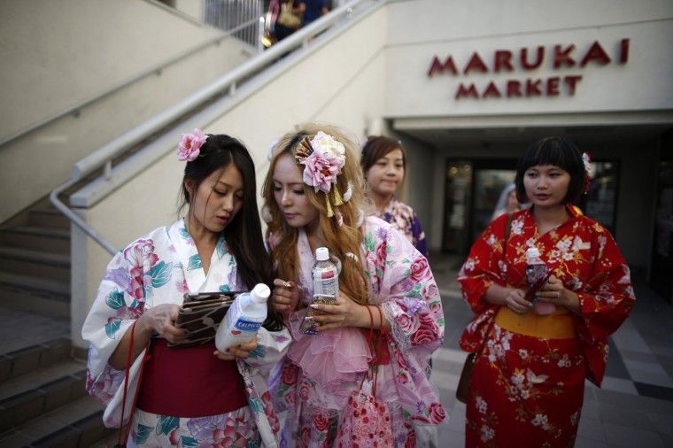 Miyako Cai (2nd L), 26, chats to friends as she walks out of a Japanese supermarket in the Little Tokyo area of Los Angeles, California August 10, 2014.