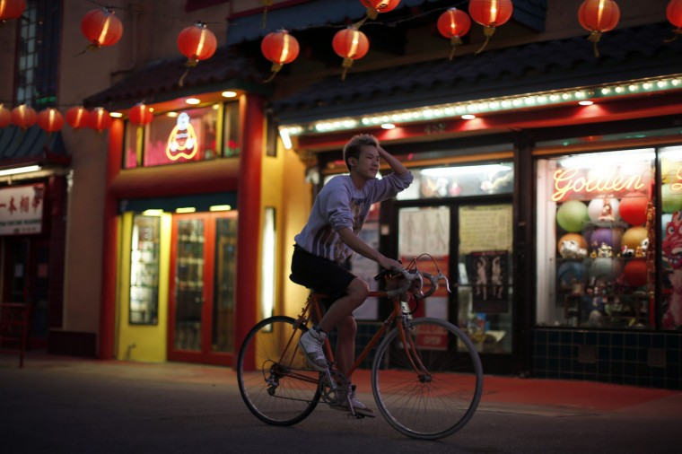 A man cycles through Chinatown in Los Angeles, California August 13, 2014.