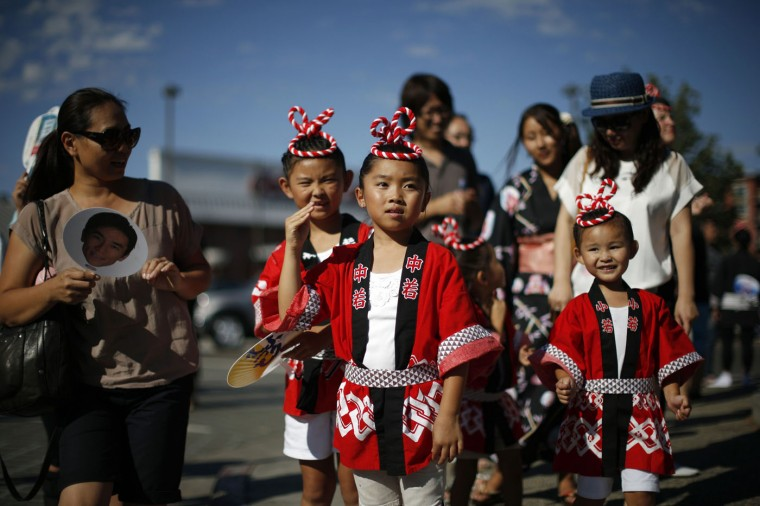 Sena Nagata, 7, Lana Osumi, 8, and Seri Nagata, 4, (L-R) wave as they watch a parade in the Little Tokyo area of Los Angeles, California August 10, 2014.