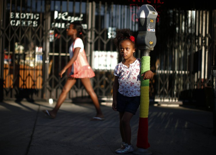 Mahlet Mogas, 5, stands with an arm around a parking meter decorated with wool in the colours of the Ethiopian flag in the Little Ethiopia area of Los Angeles, California September 14, 2014.