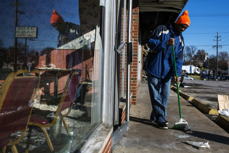 Volunteer Johnathan Johnson helps to clean a sidewalk outside of a restaurant that had been burned and damaged following a night of rioting in Ferguson, Missouri November 25, 2014. Aiming to head off new looting and rioting, Missouri's governor on Tuesday ordered National Guard reinforcements into the St. Louis suburb of Ferguson following overnight violence ignited by the clearing of a white police officer in the fatal shooting of an unarmed black teenager. (Lucas Jackson/Reuters)