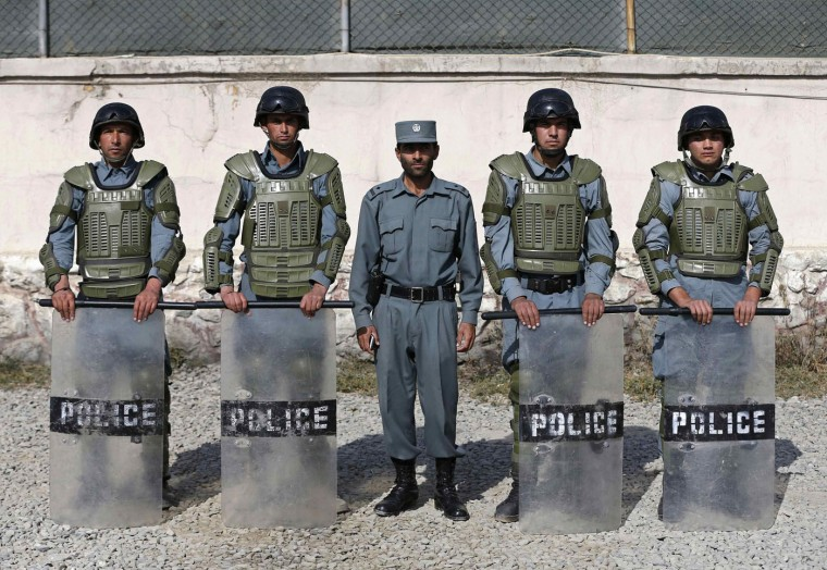 """Afghan anti-riot policemen (R-L) Habib, 21, Sayed Rahman, 22, Mohammad Nabi, 22, Momin Khan, 22, and Abdul Ali, 25, pose for photo at their base in Kabul October 12, 2014. In Afghanistan, """"the police can use weapons or explosives against a group of people only if they it has ... disturbed security by means of arms, and if the use of other means of force ... has proved ineffective"""". Afghan police are required to give no fewer than six warnings - three verbal and three warning shots - before using force in this situation. Picture taken October 12. (Omar Sobhani/Reuters)"""