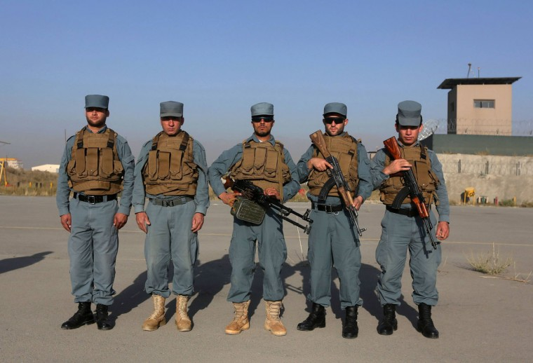 """Afghan policemen Shir Agha, 24, Shkib, 24, Qayam, 22, Farid Ahmad, 26, and Sobhan Ullah, 22, pose for photo in Kabul. In Afghanistan, """"the police can use weapons or explosives against a group of people only if they it has ... disturbed security by means of arms, and if the use of other means of force ... has proved ineffective"""". Afghan police are required to give no fewer than six warnings - three verbal and three warning shots - before using force in this situation. Picture taken October 2. (Omar Sobhani/Reuters)"""