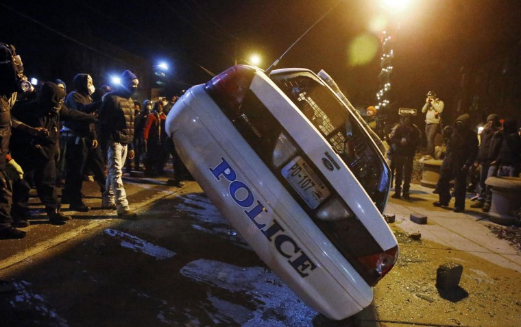 Protesters try to flip over a Ferguson police car, in Ferguson, Missouri, November 25, 2014. Missouri's governor ordered hundreds more National Guard troops to the St. Louis suburb rocked by rioting after a white policeman was cleared in the fatal shooting of an unarmed black teenager. REUTERS/Jim Young