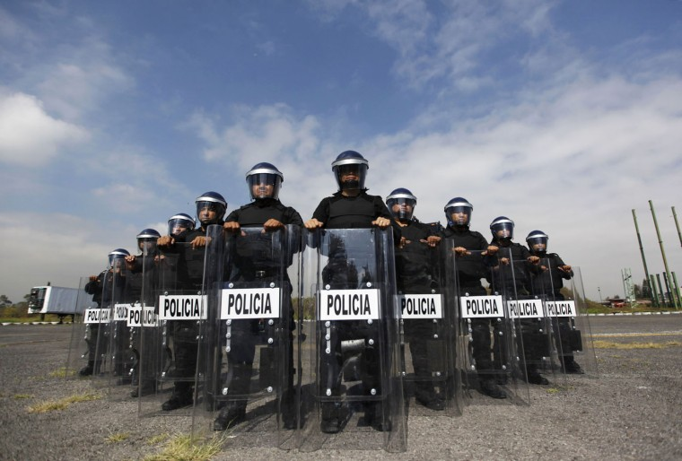 """Members of the Task Force for Mexico City at their base in Mexico City October 15, 2014. In Mexico, """"when violent action by a crowd cannot be deterred, a scale of force will be applied progressively consisting of 1. verbal persuasion or deterrence 2. reduced physical movements 3. use of non-lethal incapacitating weapons, and 4. use of firearms or lethal force"""". Picture taken October 15. (Claudia Daut/Reuters)"""