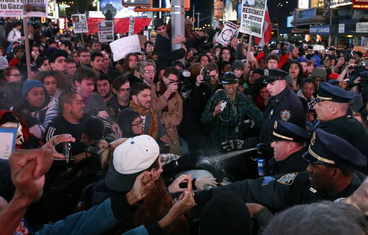 A New York City Police NYPD officer (R) uses pepper spray as police clash with people protesting against the verdict announced in the shooting death of Michael Brown, in Times Square, New York, November 25, 2014. United Nations Secretary-General Ban Ki-moon on Tuesday urged protesters in Ferguson, Missouri, and elsewhere in the United States to refrain from violence and called on law enforcement to protect the rights of people to demonstrate peacefully. REUTERS/Mike Segar