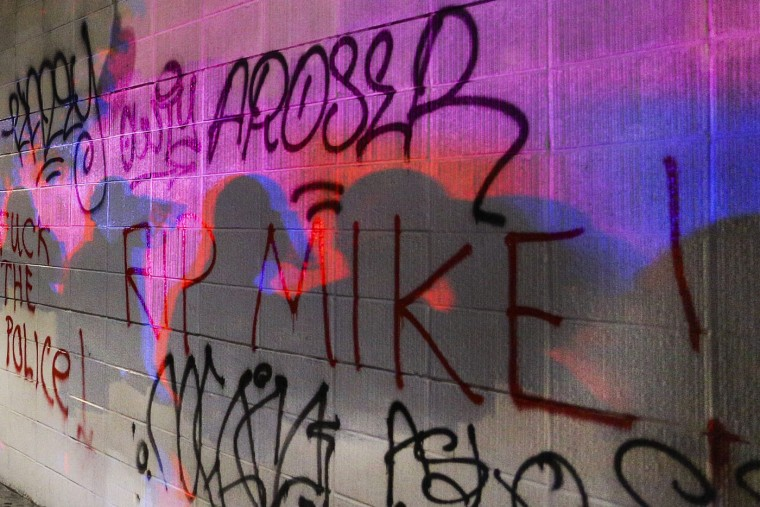 Police officers shadows are cast onto graffiti on the wall of a Subway during the second night of demonstrations in Oakland, California, following the grand jury decision in the shooting of Michael Brown in Ferguson, Missouri, November 25, 2014. (Elijah Nouvelage/Reuters)