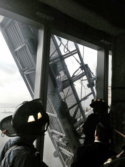 A picture tweeted by the New York City Fire Department appears to show workers trapped on scaffolding outside 1 World Trade Center in New York November 12, 2014. New York City fire fighters were trying to rescue at least one window washer on Wednesday thought to be trapped on broken scaffolding that was dangling outside the 69th floor of One World Trade Center, local officials said. (NYFD via Reuters)