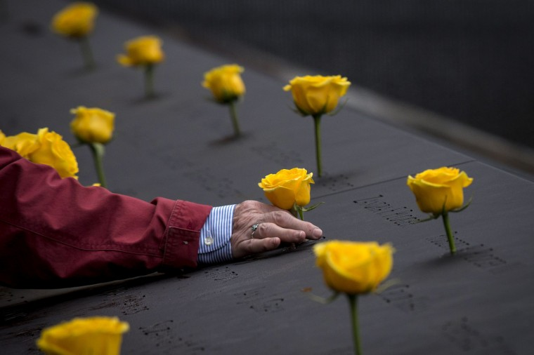 A volunteer places a flower on an inscribed name at the 9/11 Memorial in New York November 11, 2014. The 9/11 Memorial placed yellow roses on the names of veterans as a Salute to Service for Veterans Day. (Brendan McDermid/Reuters photo)