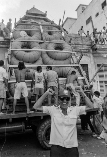 A man gestures as a makeshift boat is lowered from a roof where it was constructed by would-be emigrants, as they take it to launch into the Straits of Florida towards the U.S., on the last day of the 1994 Cuban Exodus in Havana on September 13, 1994. (REUTERS/Rolando Pujol Rodriguez)