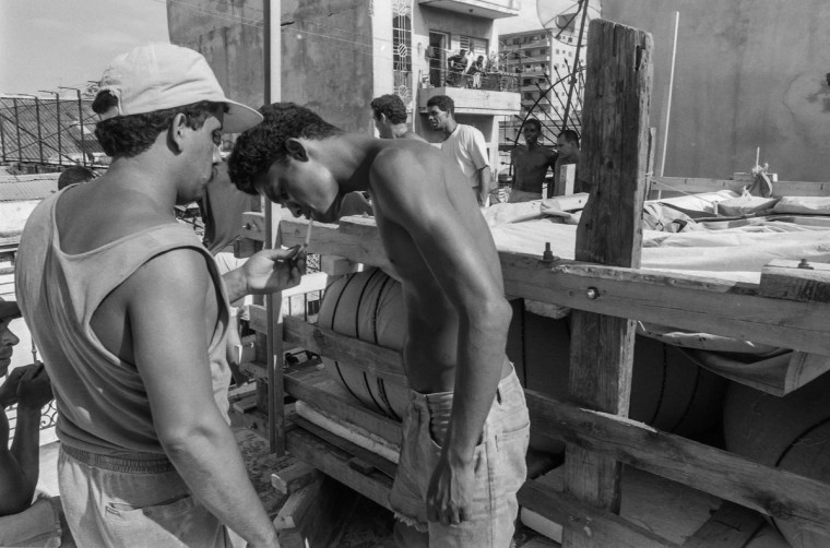 Would-be emigrants take a break while getting ready to lower their makeshift boat from a rooftop to a truck and launch it into the Straits of Florida towards the U.S., on the last day of the 1994 Cuban Exodus in Havana on September 13, 1994. (REUTERS/Rolando Pujol Rodriguez)