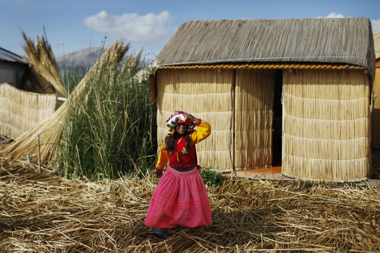 An Andean girl walks in front of her home, a straw hut, at a Uros island at Lake Titicaca in Puno on November 5, 2014. (REUTERS/Enrique Castro-Mendivil)