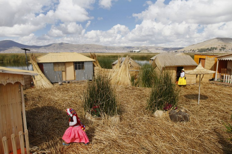 An Andean girl walks near straw huts in a Uros island at Lake Titicaca in Puno on November 5, 2014. (REUTERS/Enrique Castro-Mendivil)