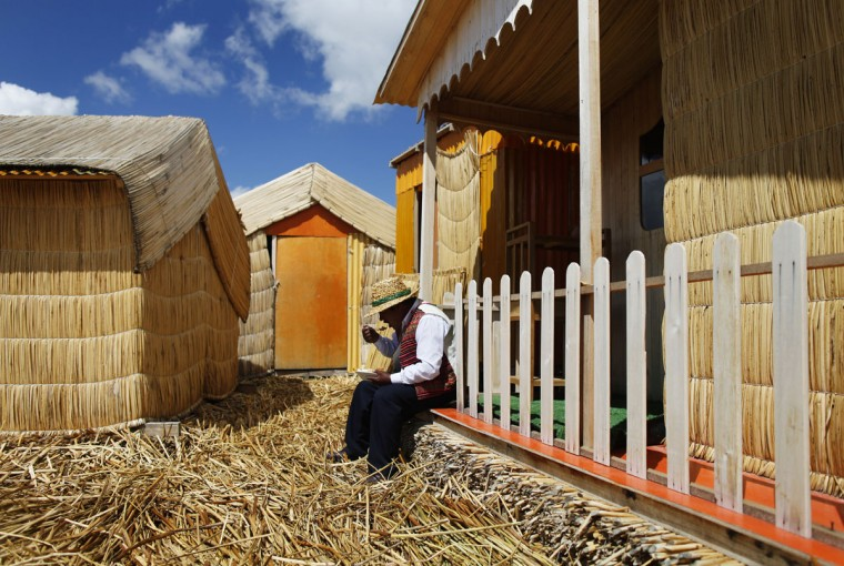 An Andean man eats outside his straw house in a Uros island at Lake Titicaca in Puno on November 5, 2014. (REUTERS/Enrique Castro-Mendivil)