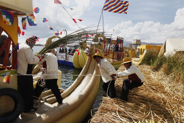 Andean people prepare a totora raft at the shores of a Uros island at Lake Titicaca before a re-enactment of the legend of Manco Capac and Mama Ocllo in Puno on November 5, 2014. (REUTERS/Enrique Castro-Mendivil)