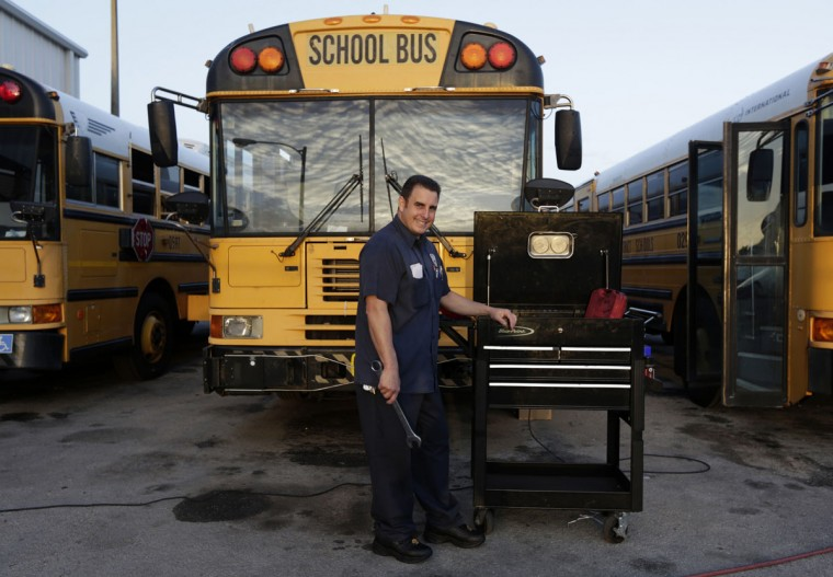 Former Cuban rafter Hanoi Lopez, 39, poses in the yard where he works as mechanic at a public school bus company in Miami on September 15, 2014. (REUTERS/Enrique de la Osa)