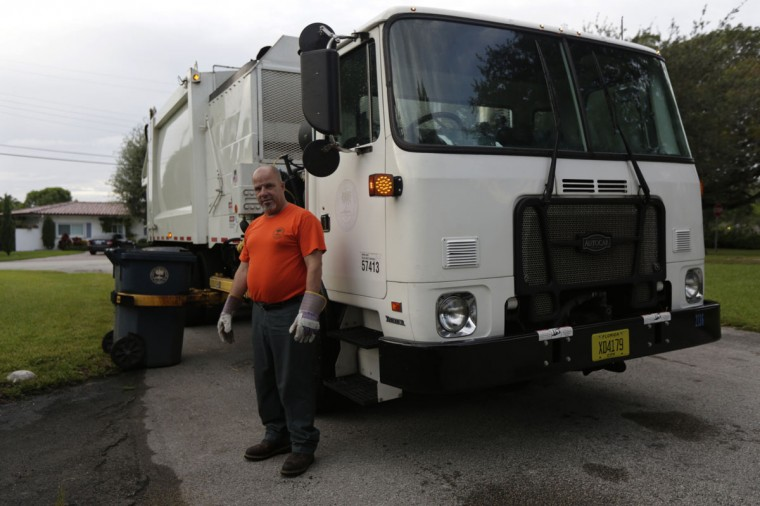 Former Cuban rafter Pedro Brea, 50, poses while working as a municipal garbage collector in Miami, September 18, 2014. Brea said he spent three days clinging to a sinking raft in the middle of a storm when a U.S. Navy frigate picked him up from the sea in 1994. (REUTERS/Enrique de la Osa)