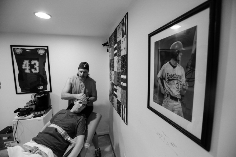 Ken exercises Ryan's arms. A portrait of Ryan during his baseball days hangs on the wall, a reminder of Ryan's past self. (Kaitlin Newman/For The Baltimore Sun)