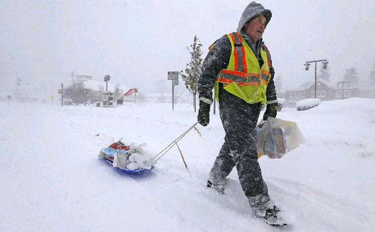 With a driving ban in place, Bill Westfall uses some ingenuity and a child's sled to retrieve groceries for his family on Main Street in East Aurora on Tuesday. (Robert Kirkham/Buffalo News)