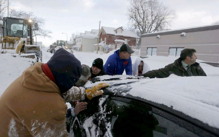 Buffalo Bills coach Doug Marrone, center in the sweatshhirt, is one of the Good Samaritans helping to free a car from the snow on Abbott Road in South Buffalo. (John Hickey/Buffalo News)