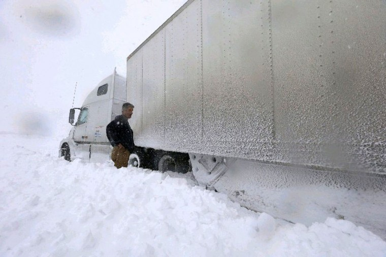 Amid stormy traffic chaos, tractor-trailer driver Omer Odovse, a native of Bosnia, checks out his rig that's stuck in snow Tuesday at the Route 219 off-ramp leading to Route 391 in the Town of Boston. (Harry Scull Jr./Buffalo News)